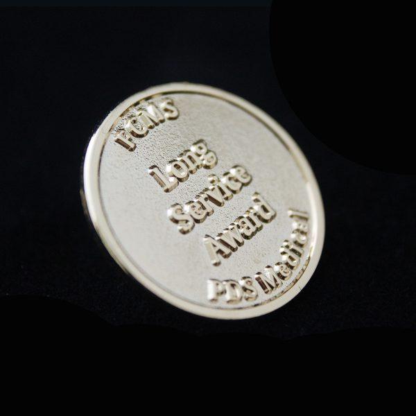 Gold Lapel pin for FCMS PDS Medical on black background