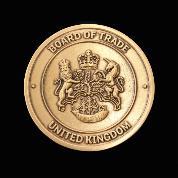 Close up of 50mm Gold Antique Smooth Commemorative Coin Board of Trade for APS Group on black background