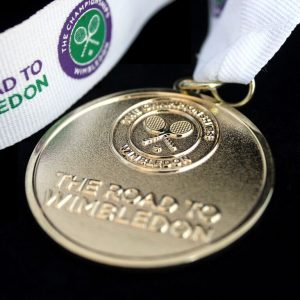 Close up of Lawn Tennis Association Road to Wimbled on Medal on black background