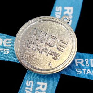 Close up of Ride Staffs Sports Pendant for Leadout Cycling Ltd wuth blue ribbon on black background