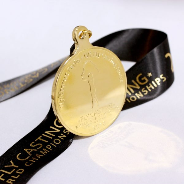 Close up of Gold Fly Casting World Championships 2018 Sports Pendant with ribbon and reflection